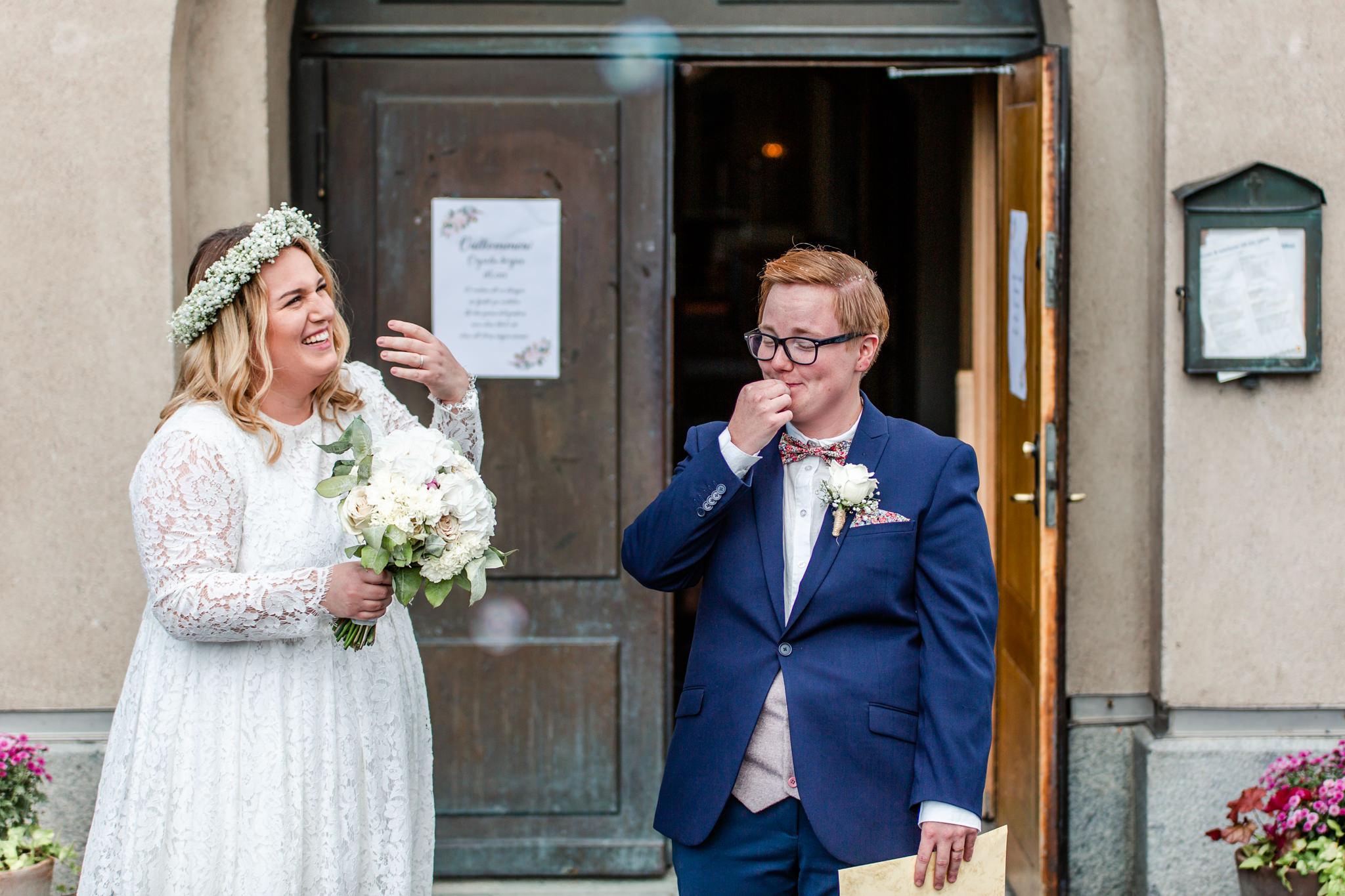 Brudpar med riskastning efter vigsel i Norrtälje kyrka